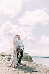 Weddings in the mountains by the rocks. The ceremony in the style of fine art. Summer walking photo shoot of newlyweds.