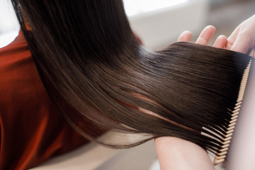 Close up. of beautiful silky hair is in hands of stylist while she combing by hairbrush