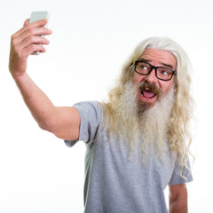 Studio shot of happy senior bearded man smiling while taking sel