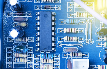 Microchip, capacitors, resistors on a blue computer board. Industrial background.