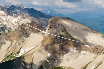 Segelflugzeug fliegt kreisend über Bergen