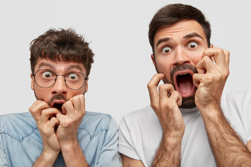 Close up shot of emotive stupefied men stare at camera with bugged eyes full of fear, keep hands near opened mouthes, stand closely to each other, isolated over white background. Shock concept Wall mural