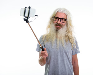 Studio shot of happy senior bearded man smiling while wearing ey