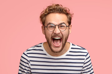 Crazy man yells loudly, has overjoyed facial expression, shouts for his favourite team, wears round transparent glasses and striped clothes, poses over pink background. Amazed hipster exclaims