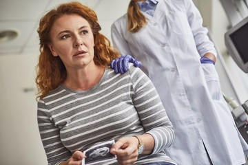 Disappointing results. Waist up portrait of middle-aged woman with sonography picture in hands. Supportive doctor in white lab coat and sterile gloves touching lady shoulder