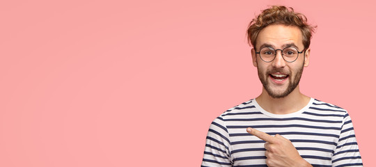 Cheerful curly man with bristle, points left, wears casual clothes and spectacles, has satisfied expression, shows free space for your slogan, promotional content or advertisemet. Look aside there Wall mural