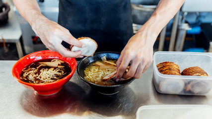 Chef adding ingredients in ramen noodle for making miso and shoyu ramen.