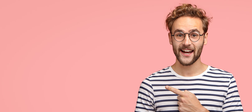Cheerful curly man with bristle, points left, wears casual clothes and spectacles, has satisfied expression, shows free space for your slogan, promotional content or advertisemet. Look aside there