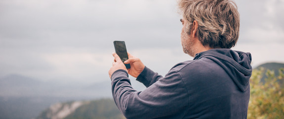 Hiking man taking panoramic picture of mountain landscape using smartphone