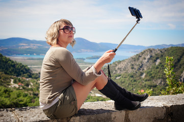 Woman taking selfie picture on landscape background using photo stick
