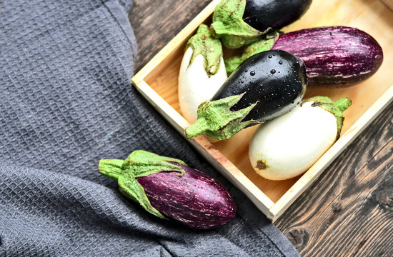 3 colorful mixed of Eggplant (Solanum melongena) or aubergine with water drop in wooden box on wooden background.