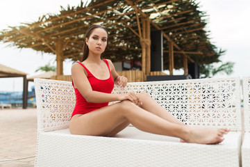 Young woman in swimsuit relaxing on sun lounger near the pool.