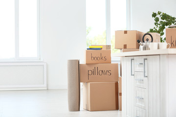 Moving boxes and household stuff in room. Space for text