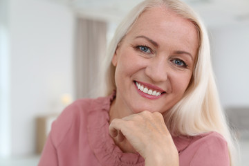 Portrait of beautiful older woman against blurred background