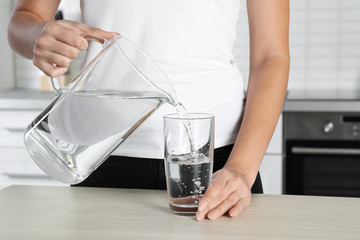 Woman pouring water into glass at table, closeup