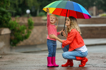 Happy mother and daughter with bright umbrella under rain outdoors