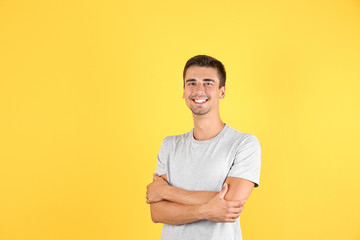 Portrait of handsome young man smiling on color background. Space for text