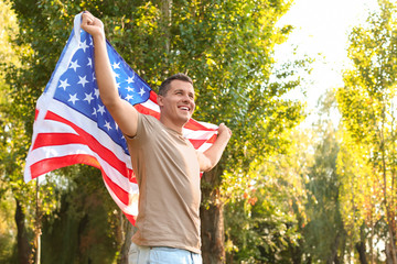 Man with American flag in park on sunny day