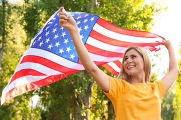 Woman with American flag in park on sunny day