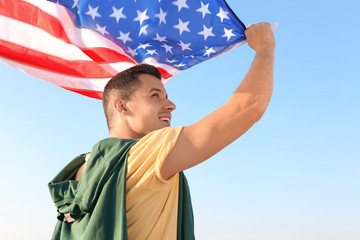 Man with American flag against blue sky