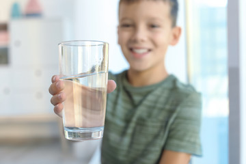 Little boy holding glass of fresh water indoors