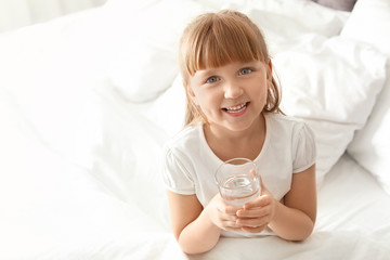 Cute little girl with glass of fresh water sitting in bed at home. Space for text