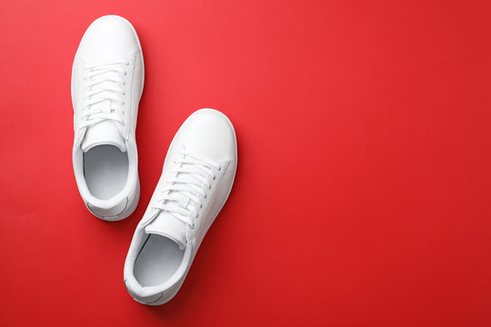 Pair of sneakers on color background, flat lay. Space for text