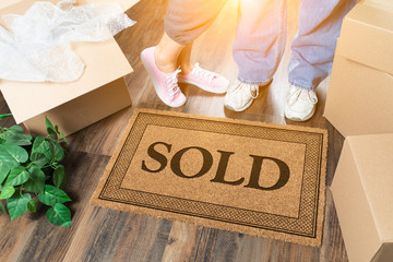 Man and Woman Standing Near Sold Welcome Mat, Moving Boxes and Plant