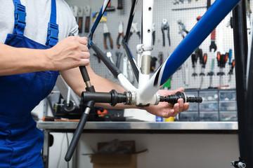 Professional mechanic repairing bicycle in modern workshop, closeup