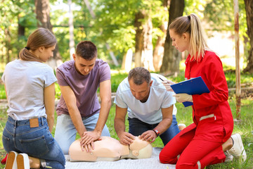 Group of people having first aid class with mannequin outdoors