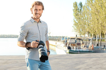 Handsome male photographer holding professional camera at pier. Space for text