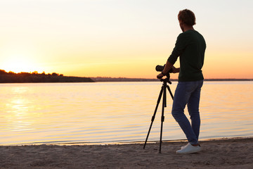 Young male photographer standing with professional camera on riverside