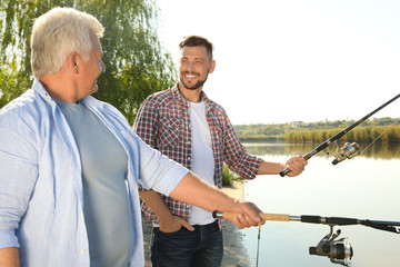 Fotobehang Vissen Father and adult son fishing together from riverside on sunny day