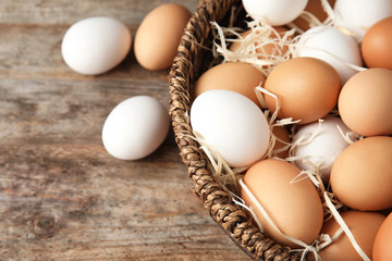 Basket with raw chicken eggs on wooden background