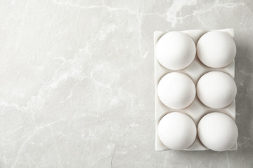 Raw chicken eggs in ceramic holder on light background, top view. Space for text