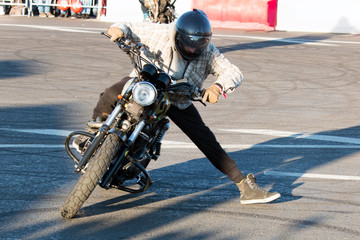 fashionably dressed biker shows tricks on a vintage motorcycle