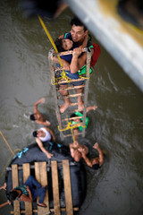 Central American migrants, part of a caravan trying to reach the U.S., use a provisional ladder to climb down from the bridge that connects Mexico and Guatemala, in Ciudad Hidalgo