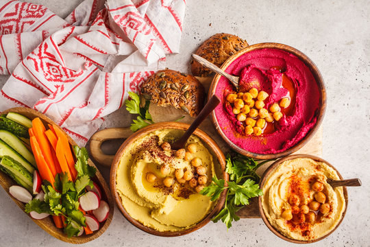 Different hummus bowls. Chickpea hummus, avocado hummus and beetroot hummus, top view.