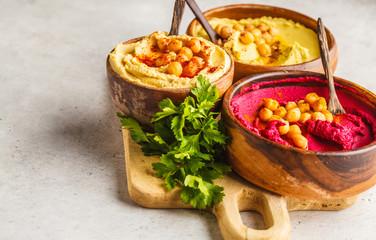 Different hummus bowls. Chickpea hummus, avocado hummus and beetroot hummus, copy space.