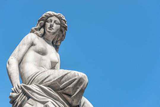 Beautiful topless girl as summit of State Opera fountain in Vienna in front of blue sky, Austria, details, closeup