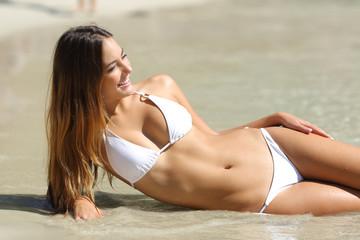 Perfect body of a woman in bikini lying on the beach