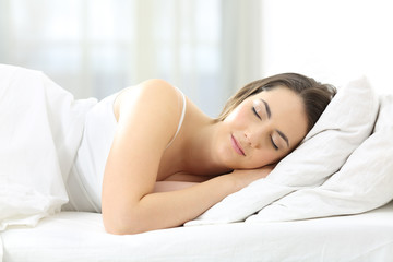 Relaxed woman sleeping on a bed at home