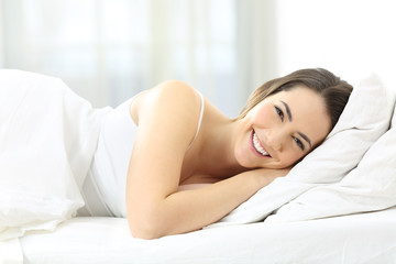 Smiley woman lying on the bed looking at you