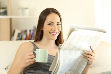 Woman holding newspaper and coffee cup looking at camera