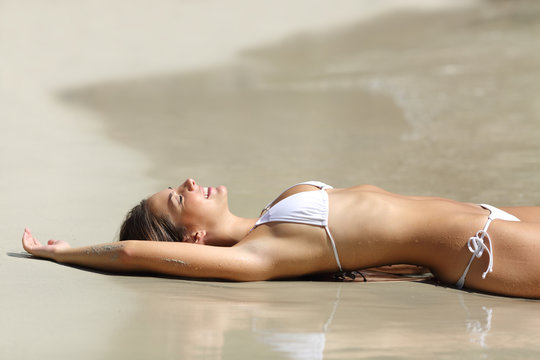 Happy woman sunbathing on the beach on vacation