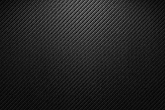 Vector carbon fiber texture. Dark background with lighting.