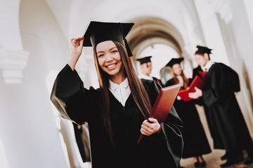 Cap. Robes. Graduate. Asian Girl. Happy. Standing.