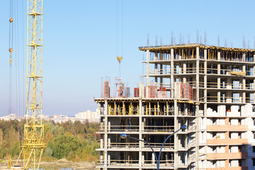 Tower cranes on the construction of a building with a frame of reinforced concrete.
