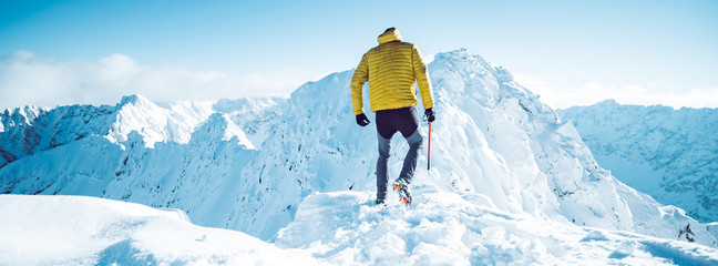 A climber ascending a mountain in winter