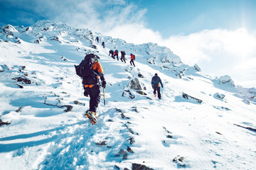 Photo sur cadre textile Alpinisme A group of climbers ascending a mountain in winter